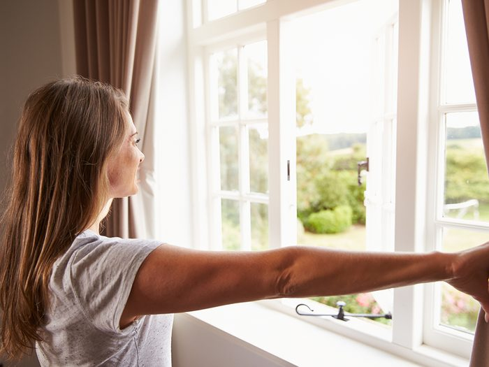 How to cool down a room without ac - woman opening window