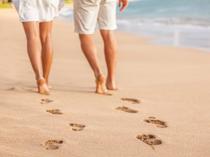 Baby terms - couple walking on beach barefoot