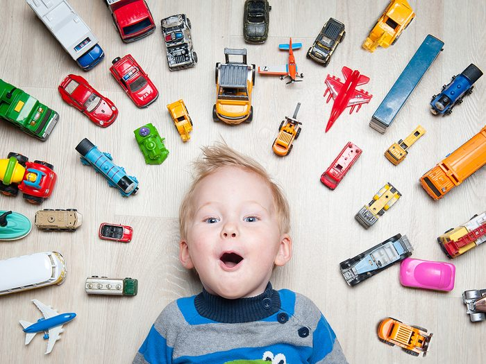 Childhood toys - child surrounded by Hot Wheels toy cars