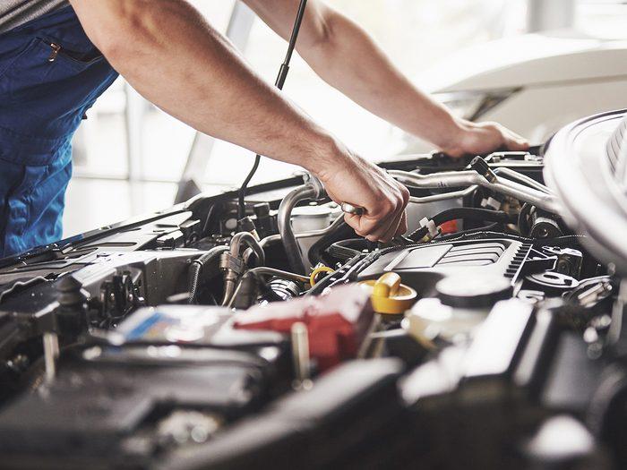 DIY car maintenance and repair - man working under hood