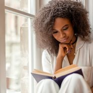 Poet Sonnet L'Abbe - Pretty afro-american girl with reading a book sitting on the windowsill.